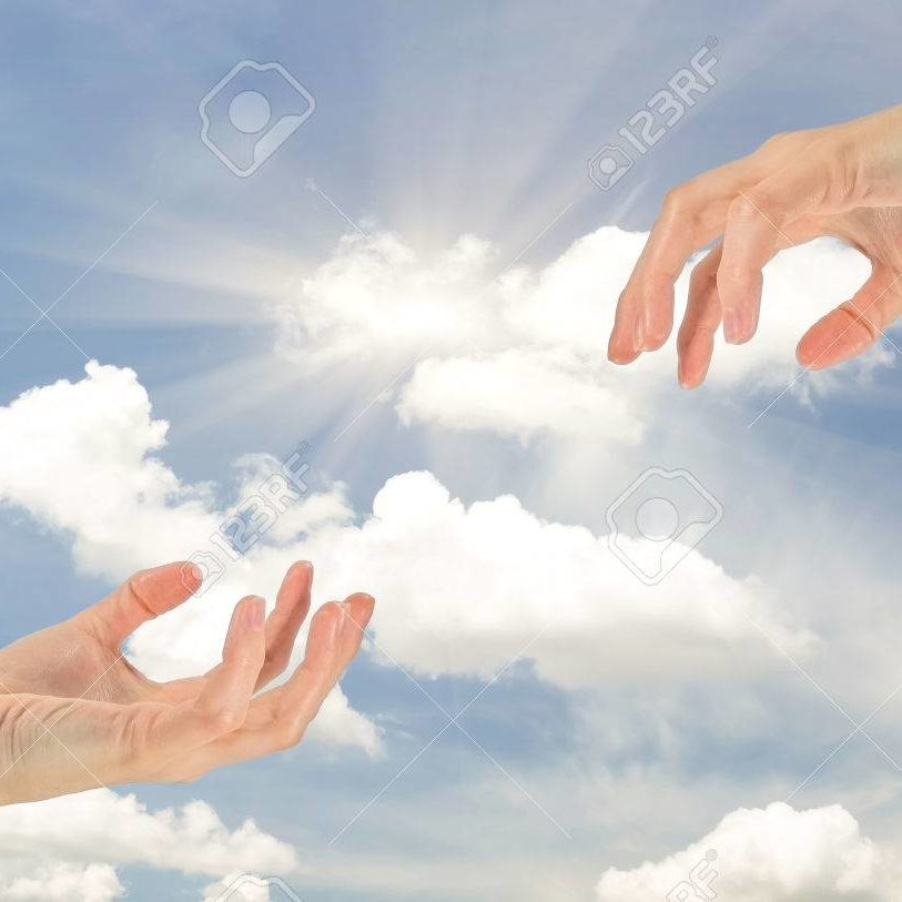 Concept of religion and God. Two hands reaching out to each other on the background of the cloudy sky